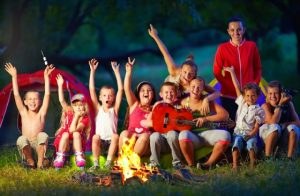 happy-kids-singing-songs-around-camp-fire